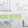 Image of a white board with the word statistics amid charts and graphs